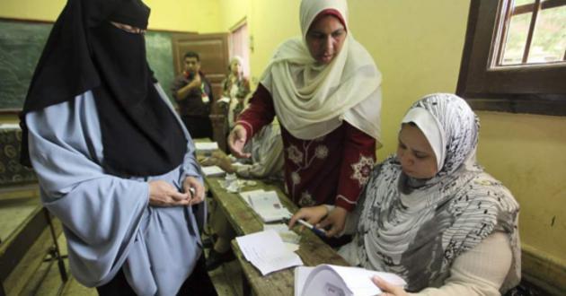 Una mujer egipcia deposita su papeleta en las urnas