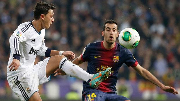 Özil controlando un balón ante la marca de Busquets.