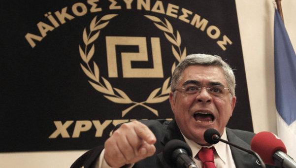 Nikolaos Michaloliakos, líder de Amanecer Dorado en una rueda de prensa donde obligaba a los periodistas a levantarse ante su llegada.