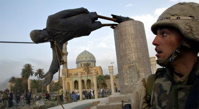 Un soldado observa el derribo de la estatua de Saddam Hussein 20 días después del inicio de la invasión (Reuters)