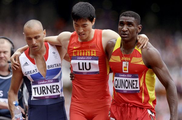Liu Xiang es ayudado por Andrew Turner y Jackson Quinonez. | FOTO: Anja Niedringhaus - AP