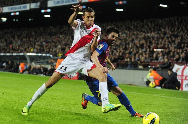 Pedro Botelho disputando un balón con David Villa
